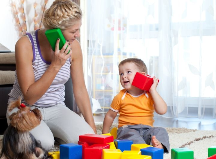 mother playing pretend telephone with little boy using building blocks