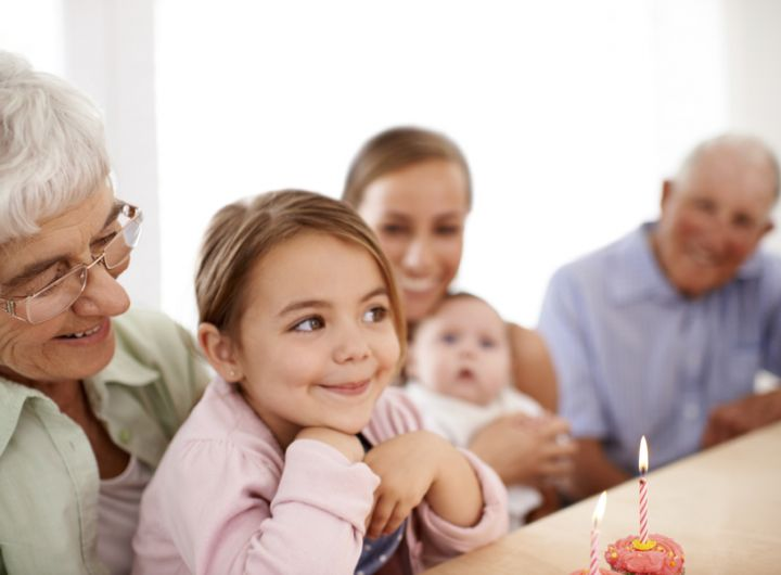 granddaughter ready to blow out cake candle sits on grandmother's lap, other family look on