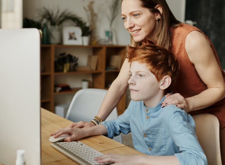 woman looks over shoulder of boy using computer