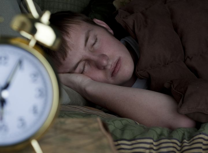 Teen_boy_snoozing_with_alarm_clock_iStock_8820264_LARGE.jpg